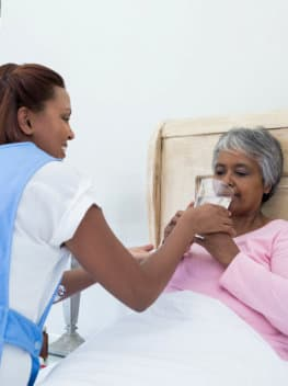 caregiver helping a senior woman drink water