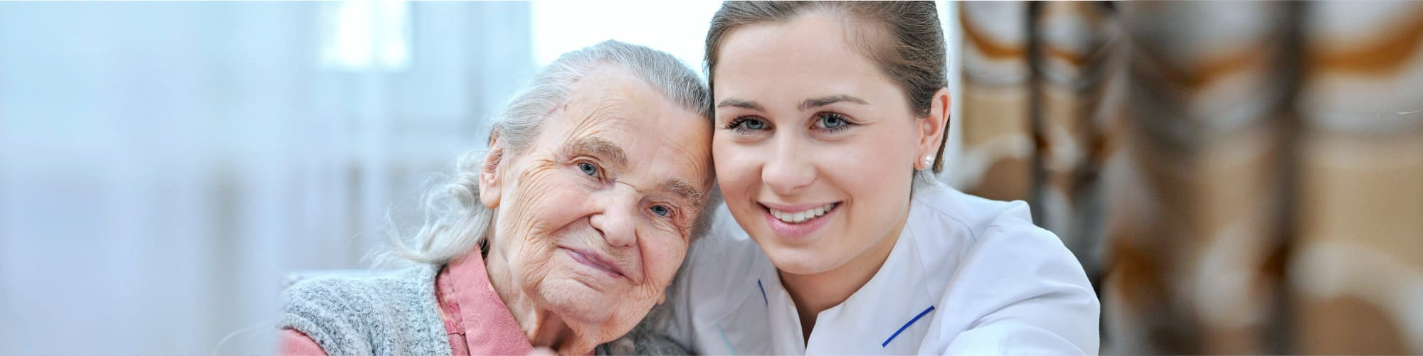 happy senior woman leaning into her caregiver's shoulder