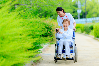 happy senior woman in a wheelchair and her caregiver