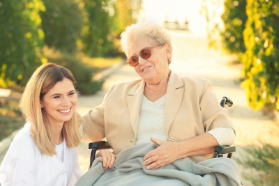 senior woman in wheelchair and caregiver smiling