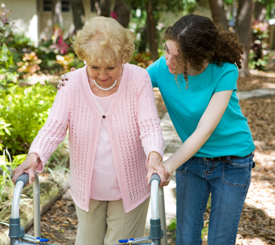 senior woman assisted to walk with the help of a walker and her caregiver