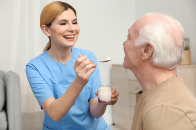 caregiver feeding senior man with