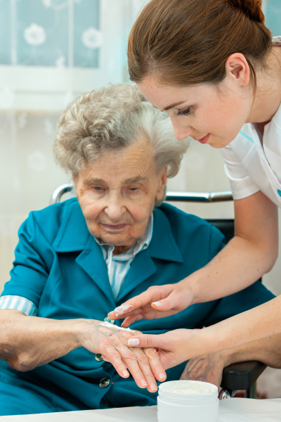 nurse putted a cream on the hand of the senior woman