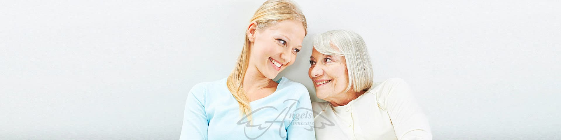 Young women and old senior women smiling at each other